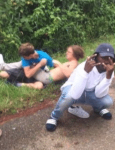 Black guy posing in front of white kids fighting / wrestling Black Twitter meme template