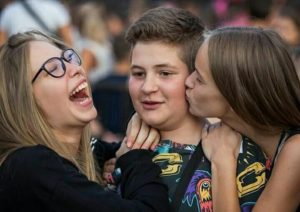 Confused boy and two girls laughing and kissing him on the cheek IRL meme template