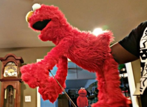 Fisting Elmo while another Elmo watches Shocked meme template